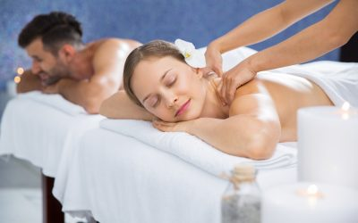 Couple getting massage together in spa center. Young Caucasian woman with flower in hair getting back massage. Man lying on massage table and relaxing after treatment in background