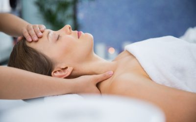 Profile portrait of young Caucasian woman lying on back, keeping her eyes closed while therapist massaging her head and shoulders. Spa concept